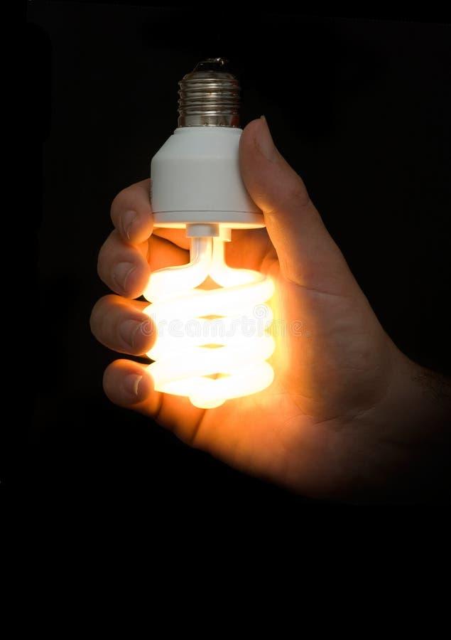 сбережениа светильника руки энергии стоковые фото