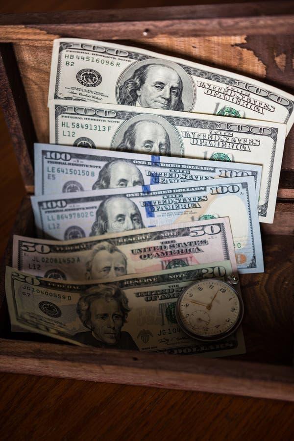 Сбережения в долларах, который хранят в старой деревянной коробке с старыми часами стоковое фото rf