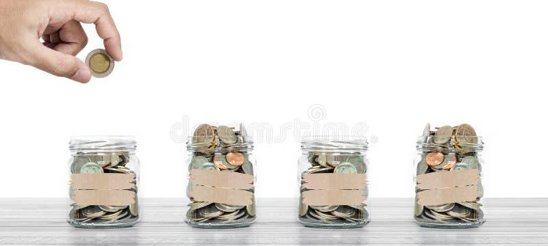Сбережения денег, рука кладя монетку в стеклянный опарник с монетками внутрь, на деревянную таблицу и белую предпосылку стоковое изображение