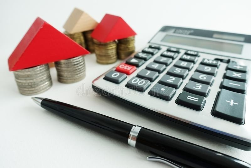 Сбережения и вычисление для вкладов недвижимости, с символом дома от монеток и деревянных частей, калькулятора и ручки на столе стоковое изображение