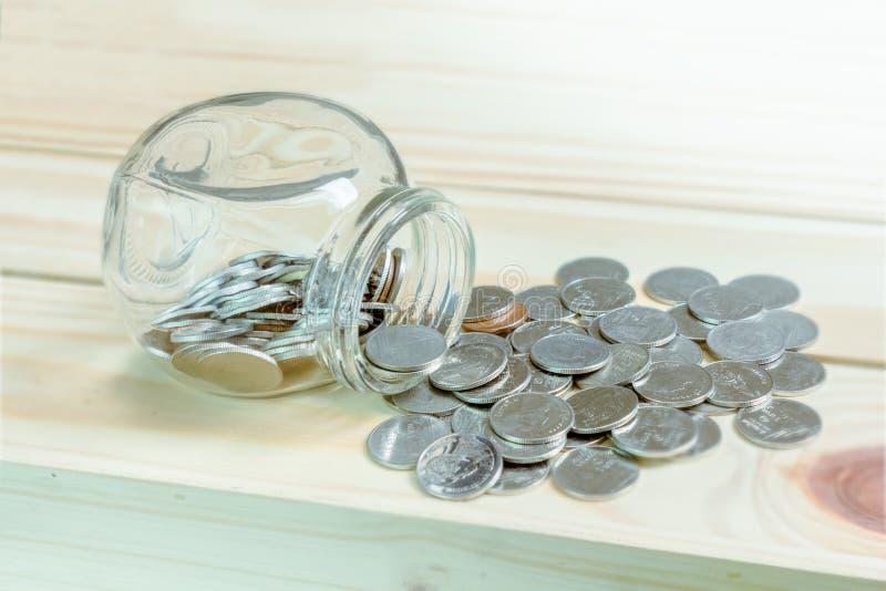 Сбережения концепции и финансовое с монетками разливая из стеклянной бутылки на деревянном столе стоковые фото