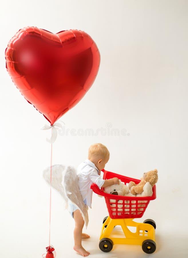 сбережения на приобретениях Ребенок мальчика в магазине игрушки мальчик идет ходить по магазинам с полной тележкой День и влюблен стоковое изображение