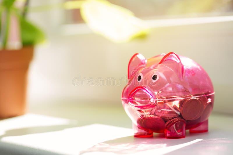 Сбережения дома - копилка на силле окна стоковая фотография