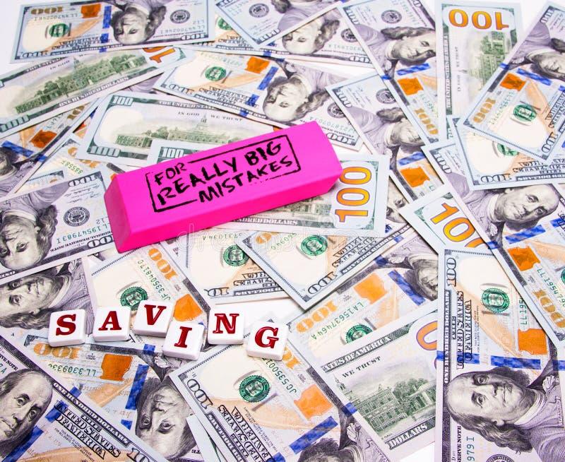 Сбережения: Разбросанный 100 долларовым банкнотам с розовым ластиком для действительно больших ошибок стоковая фотография