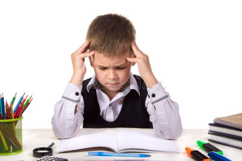 Сбиванный с толку заботливый зрачок сидя на столе с руками над головой окруженной с канцелярскими принадлежностями стоковое фото rf