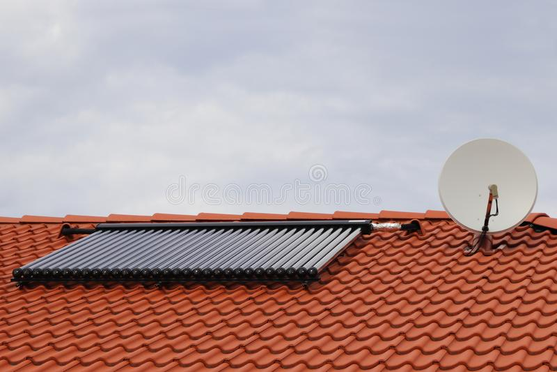 Сборники вакуума - солнечная система отопления воды на красной крыше дома со спутником стоковая фотография