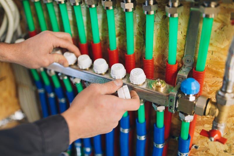 Сборник отопления под полом коллекторный с трубами, руками балансируя температуру стоковые фотографии rf