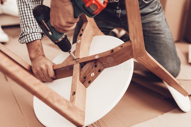 Сборщик мебели с руками сверла внутри ремонтирует стул стоковые фотографии rf