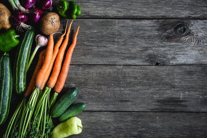 Сбор овощей на старой деревянной предпосылке картошка луков урожая морковей свеклы осени стоковая фотография