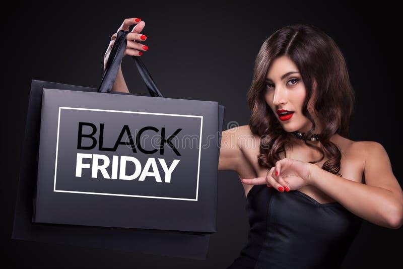 сбывание Молодая женщина показывая хозяйственную сумку в черном празднике пятницы стоковое изображение rf