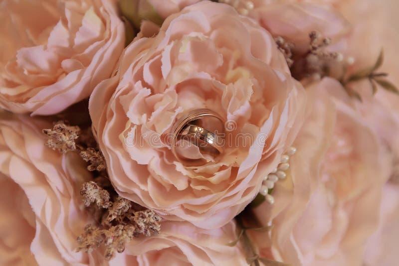 Свадебные кольца на свадебном букете с жемчужными цветами стоковые изображения rf