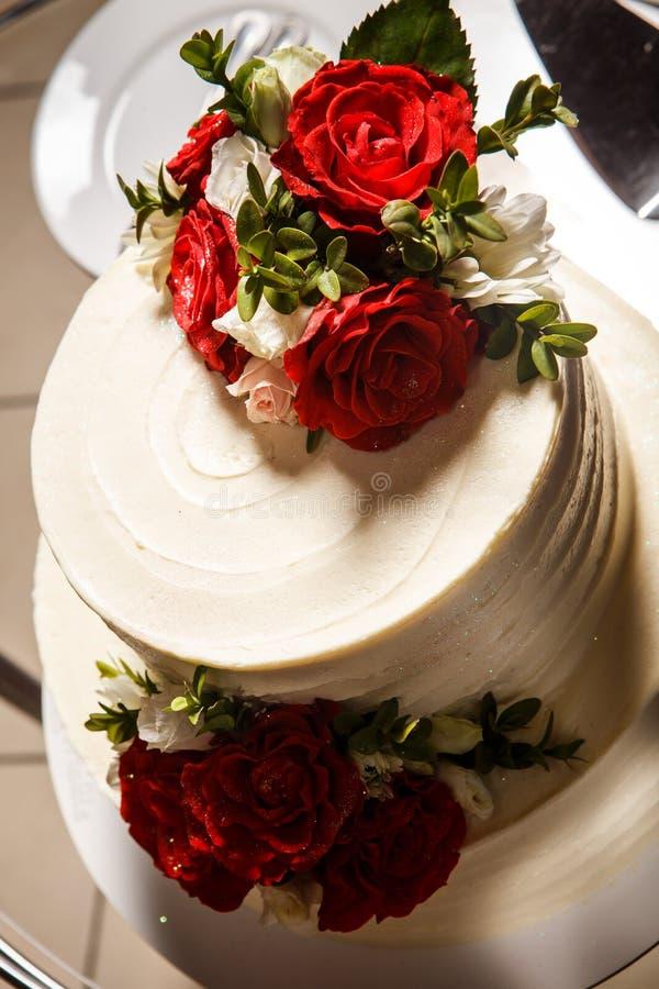свадебный пирог крупного плана взгляда сверху сметанообразный с красными розами стоковое фото