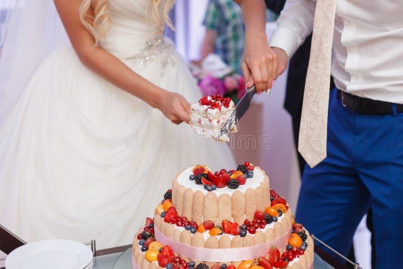 Свадебный пирог с ягодами Жених и невеста отрезал сладостный торт на банкете в ресторане стоковое изображение rf