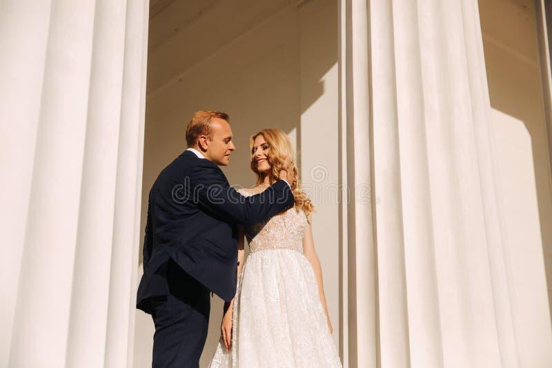 Свадьба в Греции Пары смотрят друг к другу и улыбка Падение невесты светлых волос в любовь стоковое фото
