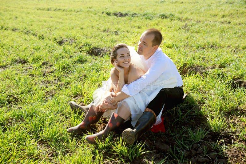 Свадьба в деревне, холит и невеста имеет потеху на траве поля стоковые фото