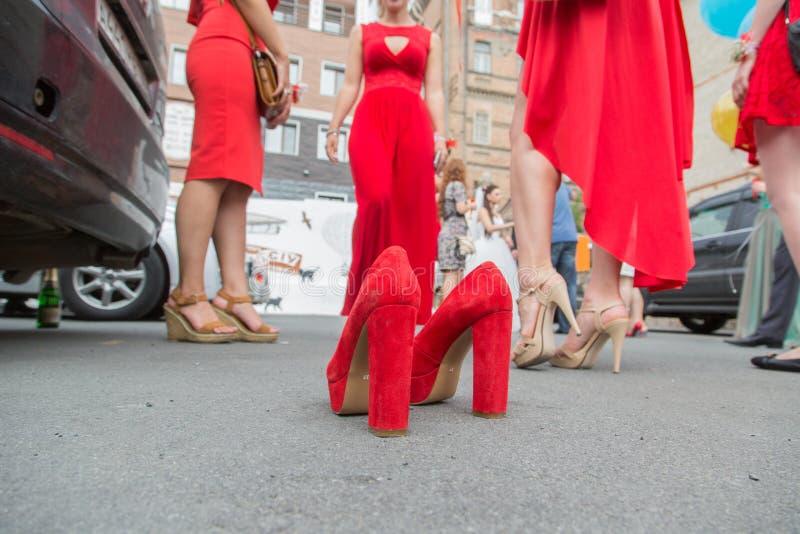 Свадьба, на мостовой красные ботинки на заднем плане bridesmaids стоковые фотографии rf