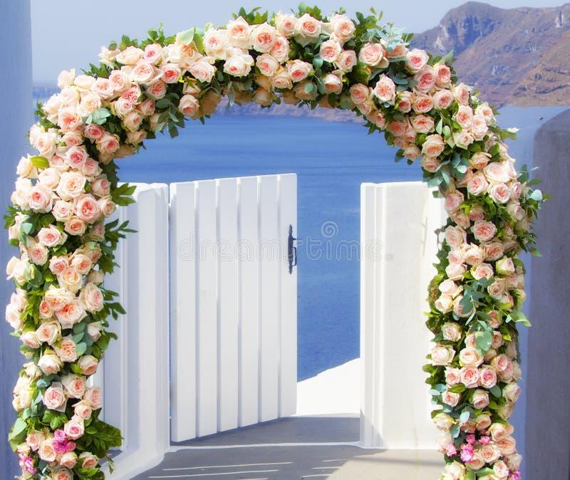 Свадьба на Santorini Красивый свод украшенный с цветками роз с голубой церковью Oia, Santorini, Греции самое большее романтичной стоковое изображение