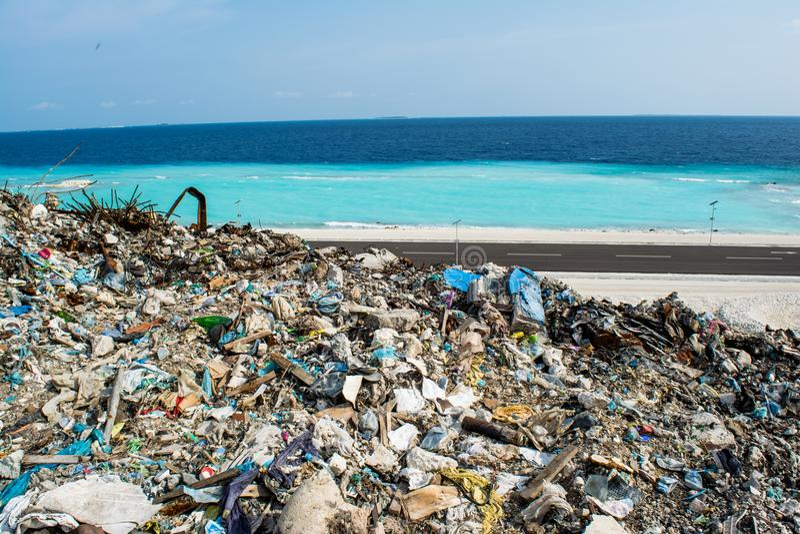 Свалка мусора около пляжа близко к океану вполне дыма, сора, пластичных бутылок, хлама и погани на тропическом острове стоковые изображения rf