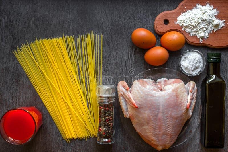 сваренное спагетти лапшей Сырые спагетти и сырцовый цыпленок на борту Ингридиенты для самодельных яичек цыпленка лапшей стоковое фото rf