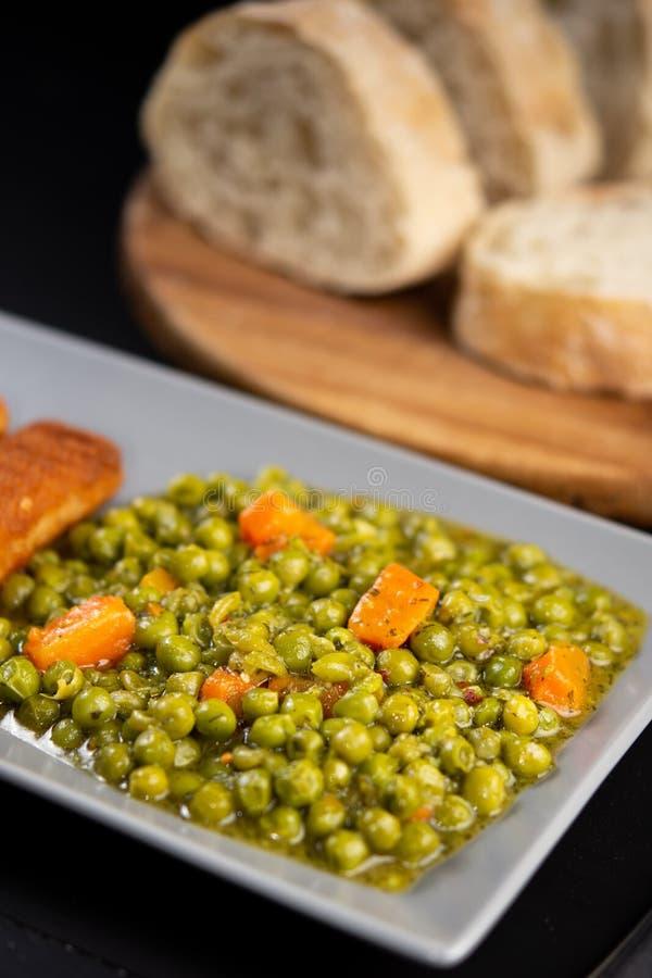 Сваренные зеленые горохи с морковью и овощами стоковые фото
