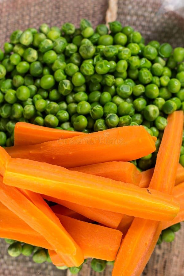 Сваренные зеленые горохи с сваренным отрезанным положением квартиры моркови стоковые фотографии rf