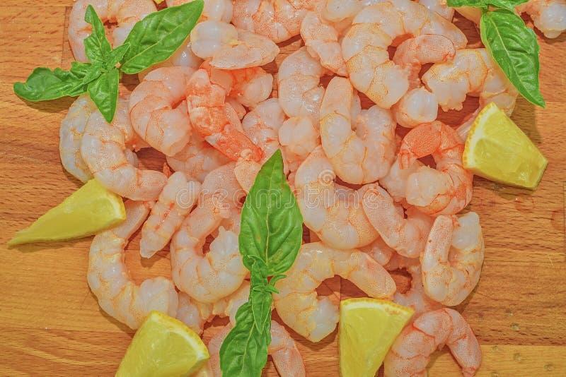 Сваренные и, который слезанные креветки с кусками лимона и листьев базилика на прерывая доске сопровоженный столб съемки еды архи стоковое фото