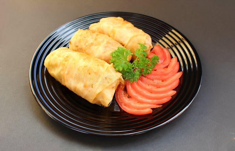 Сваренные маргаритки на плите с томатами и травами стоковые изображения