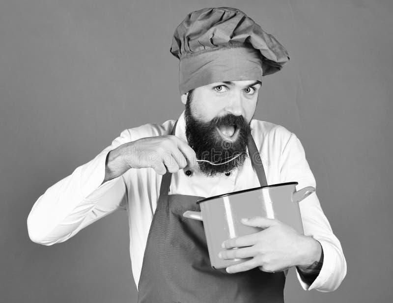 Сварите с голодной стороной в бургундской шляпе и рисберма держит бак и ложку Человек с бородой держит kitchenware на зеленом цве стоковое изображение rf