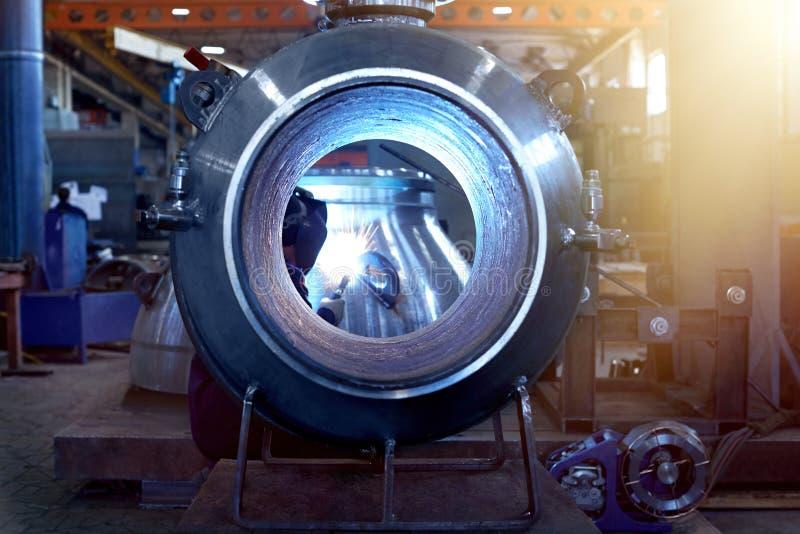 Сварщик в изумлённых взглядах и шлеме, структурах металла сварок стоковое фото