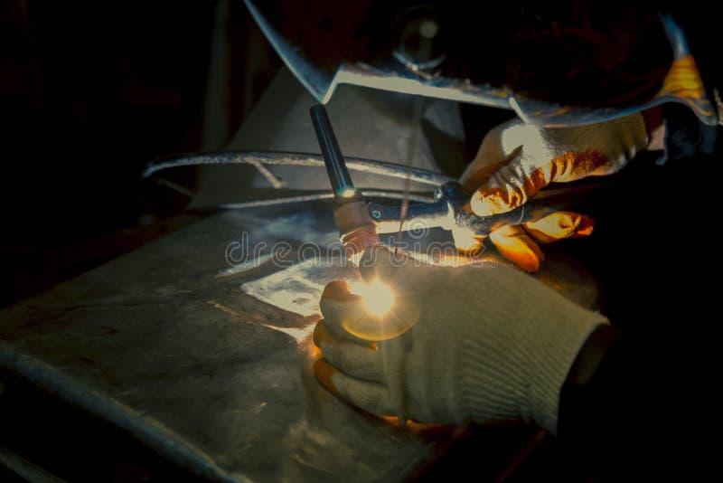 сварщик заварки Аргон-дуги на рабочем месте сваривает часть стоковая фотография