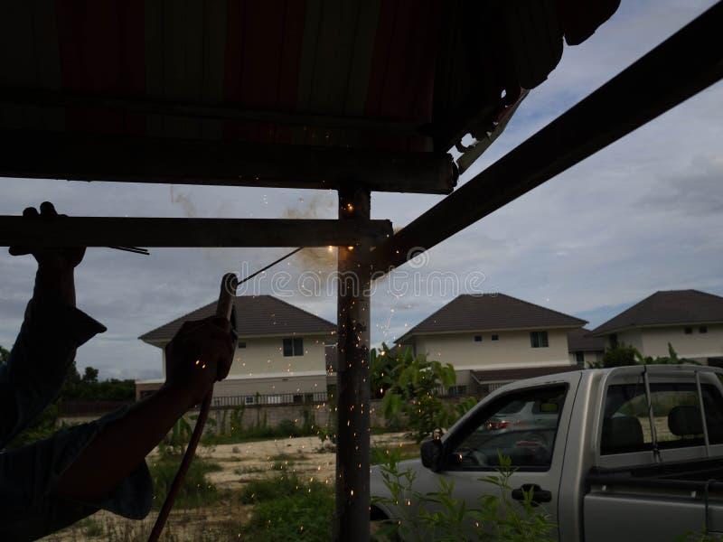 Сварщик используя электрод сваривая железный каркас, заварку искрится свет и дым стоковое фото