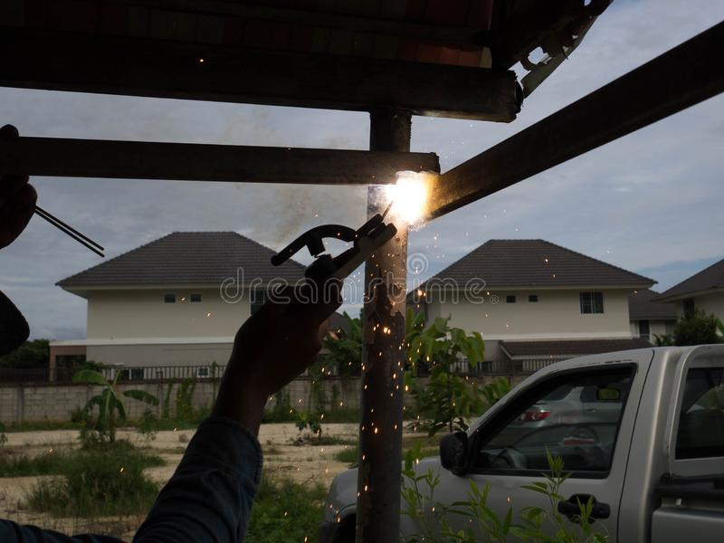 Сварщик используя электрод сваривая железный каркас, заварку искрится свет и дым стоковое фото rf