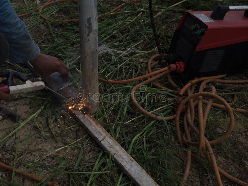 Сварщик используя электрод сваривая железный каркас со сварочным аппаратом, заваркой искрится свет и дым стоковая фотография rf