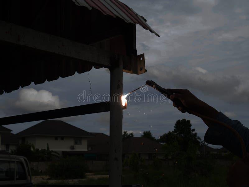 Сварщик используя электрод сваривая железный каркас со сварочным аппаратом, заваркой искрится свет и дым стоковое фото