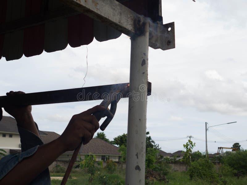 Сварщик используя электрод сваривая железный каркас со сварочным аппаратом, заваркой искрится свет и дым стоковые фото