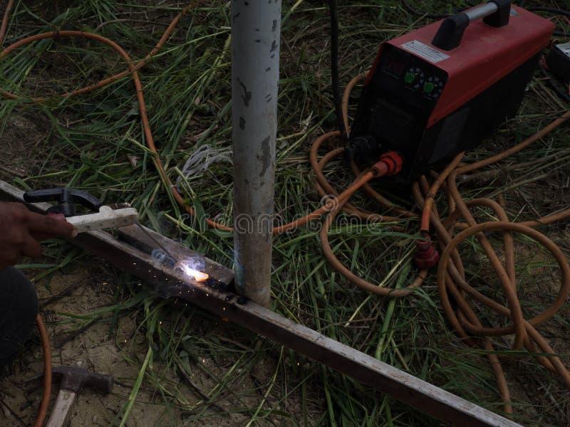 Сварщик используя электрод сваривая железный каркас со сварочным аппаратом, заваркой искрится свет и дым стоковое изображение rf