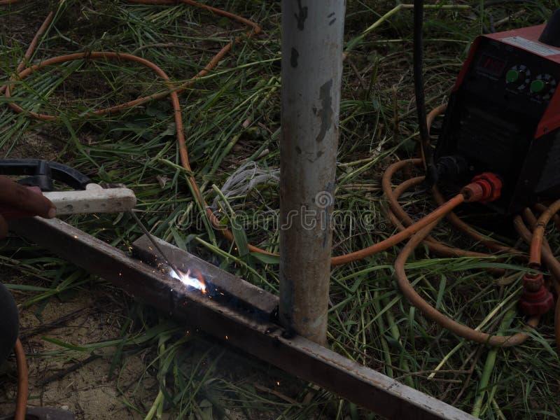 Сварщик используя электрод сваривая железный каркас со сварочным аппаратом, заваркой искрится свет и дым стоковое изображение