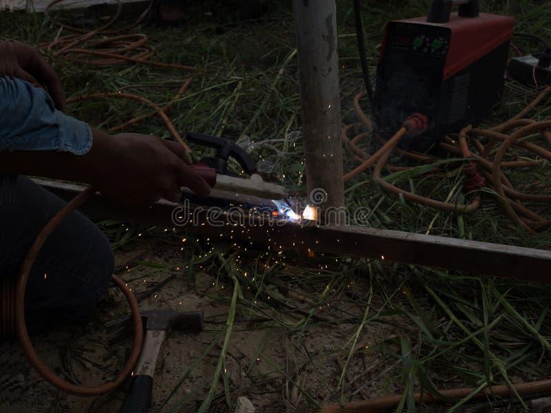 Сварщик используя электрод сваривая железный каркас со сварочным аппаратом, заваркой искрится свет и дым стоковое фото rf