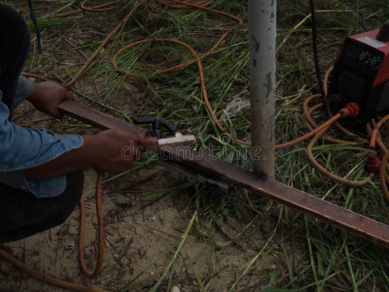 Сварщик используя электрод сваривая железный каркас со сварочным аппаратом, заваркой искрится свет и дым стоковая фотография