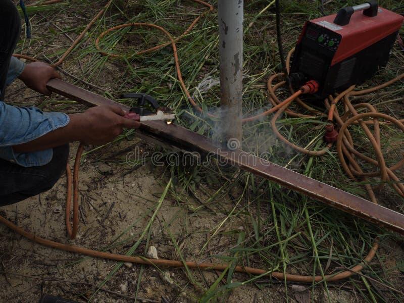 Сварщик используя электрод сваривая железный каркас со сварочным аппаратом, заваркой искрится свет и дым стоковые фотографии rf
