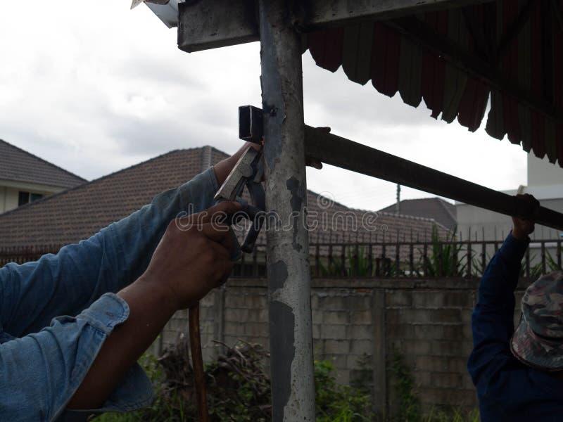 Сварщик команды используя электрод сваривая железный каркас со сварочным аппаратом, заваркой искрится свет и дым стоковые изображения rf