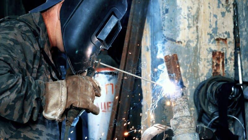 Сварщик на фабрике в сваривая частях металла сварок маски Рамка Замаскированные части сварщика сваривая Заварка с голубым и стоковые изображения rf