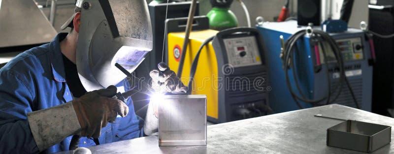 Сварщик работает в конструкции металла - конструкция и обработка стоковое изображение