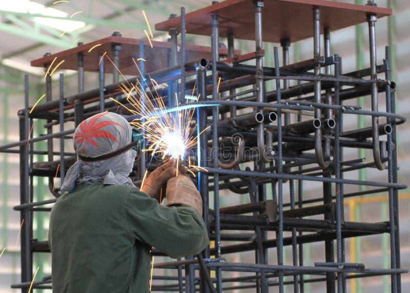 Сварщик сваривает железный каркас в фабрике стоковые фото