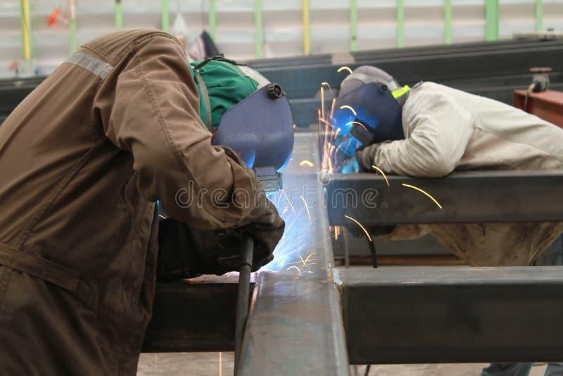 Сварщик 2 сваривает стальную структуру с всем оборудованием для обеспечения безопасности в фабрике стоковые изображения