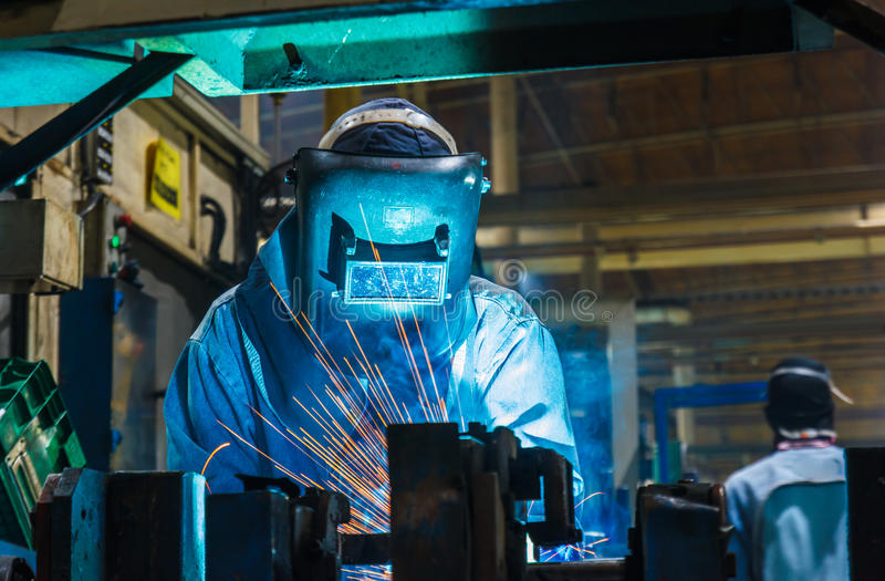 Сварщик, сваривая автомобильная деталь в фабрике автомобиля стоковые фото