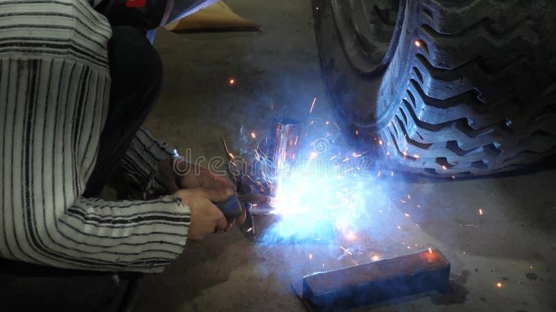 Сварщик соединяет части металла со сложными структурами используя электрическую сварку красочные искры летают к стороне стоковая фотография rf