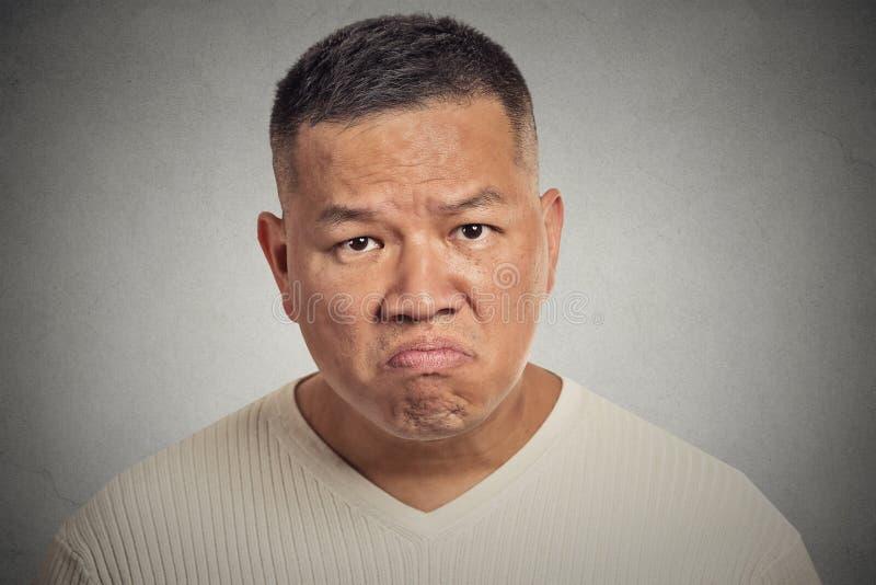 Сварливый человек изолированный на серой предпосылке стоковая фотография