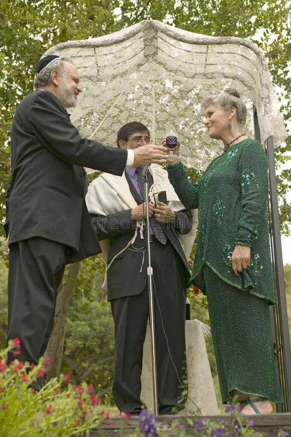 Свадебная церемония под сенью с равином, женихом и невеста на традиционной еврейской свадьбе в Ojai, CA стоковое фото