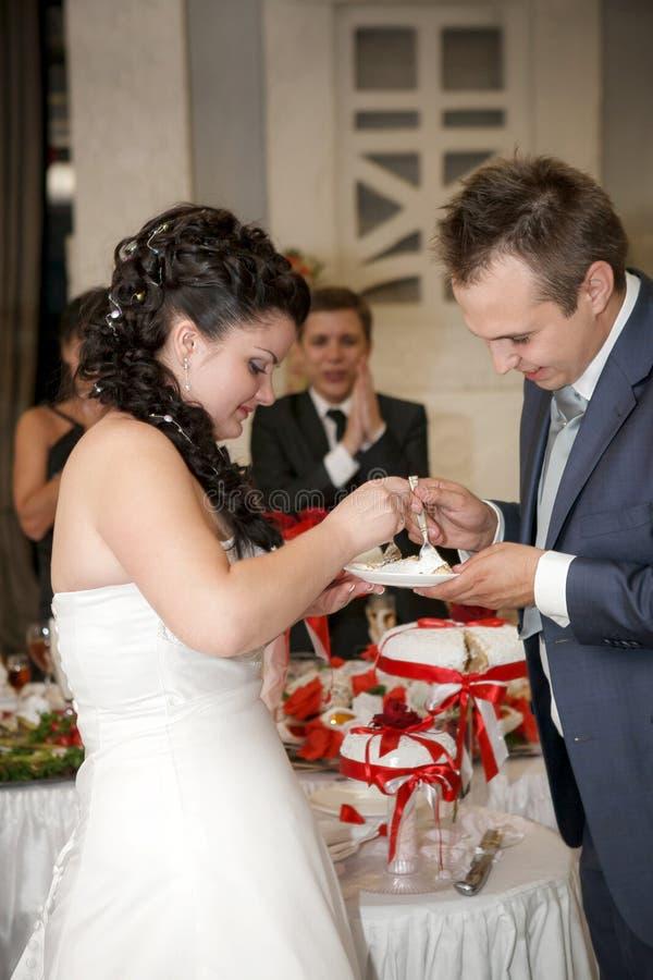 Свадебный пирог невесты подавая к Groom стоковая фотография rf